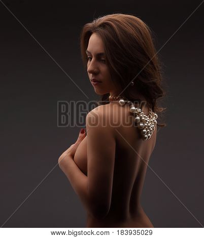 Young Brunette Model Over Dark Background Naked With Necklace Hiding Her Chest And Looking Down