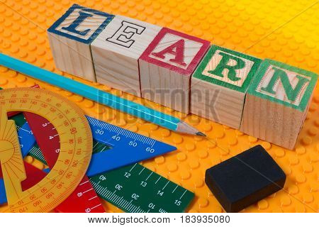 Learn Word Written In Wooden Cube On Yellow Plastic With School Stationery Tools. Learn Concept Back