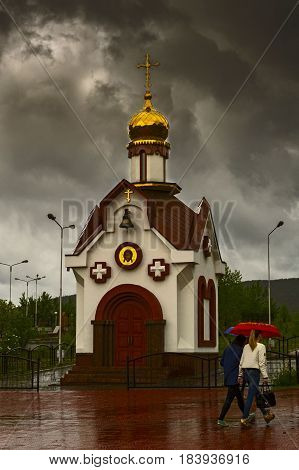 Orthodox Church against the dramatic sky on rainy day. People walk under an umbrella.