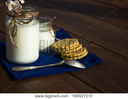 Two jars of fermented milk product with silver spoon and cookies on wood background