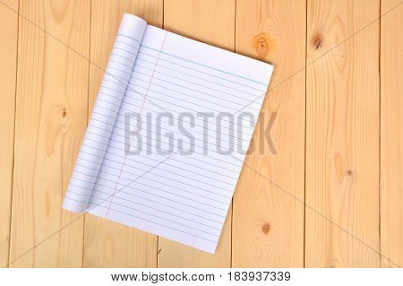 Notebook open to show white paper on wooden background.