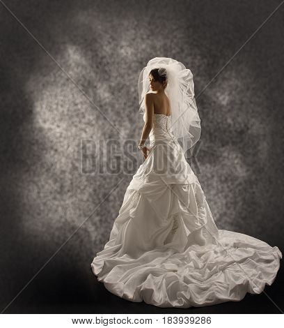 Bride in Wedding Dress with Veil Fashion Bridal Beauty Portrait Rear View Looking Back over Shoulder Long Draped Cloth with Folds