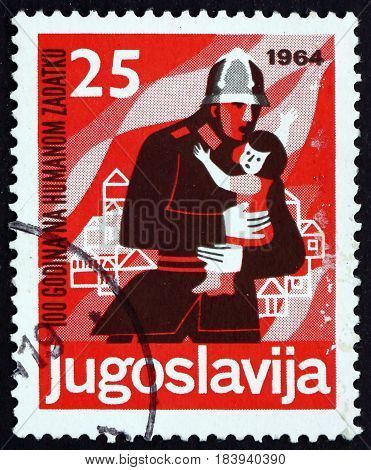 YUGOSLAVIA - CIRCA 1964: a stamp printed in Yugoslavia shows Fireman Rescuing Child Centenary of Voluntary Fireman circa 1964