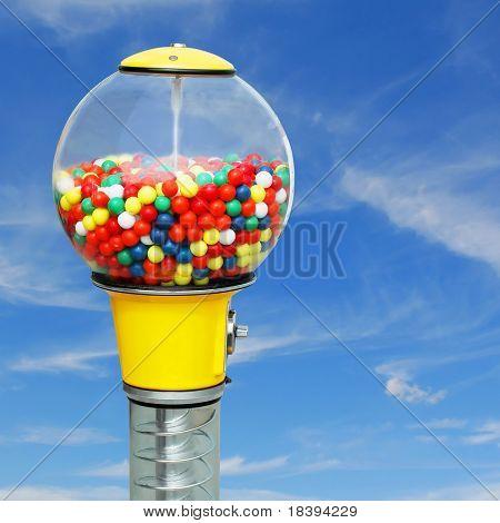 Kaugummiautomat mit bunten Kaugummi Kugeln auf quadratische blauer Himmel Hintergrund
