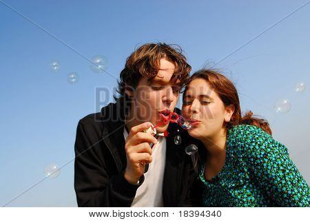Concept: stay young! Young couple in their twenties blowing soap bubbles together with blue sky background