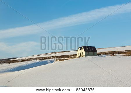 Little house over snow covered high hill Iceland winter season landscape background
