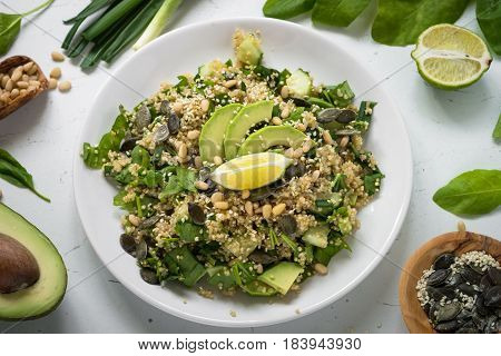 Fresh quinoa salad with spinach avocado greens seeds and Pine nuts. Clean eating detox and vegetarian food. Top view on white.