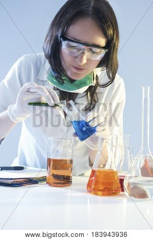 Medicine and Healthcare Concepts. Female Laboratory Staff Dealing with Flasks Filled with Chemicals Specimens During Scientific Experiment in Laboratory. Vertical Image