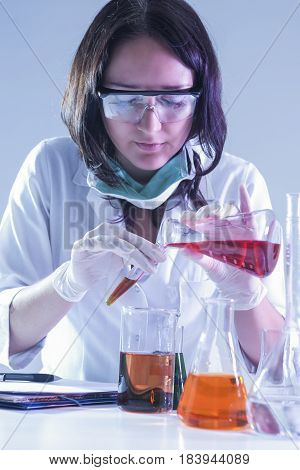 Medicine Ideas and Concepts. Female Laboratory Worker With Flasks Filled With Liquid Chemicals Conducting Experiment.Vertical Shot