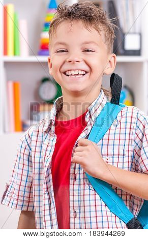 Half-length emotional portrait of caucasian boy. Funny smiling teenager with school bag. Handsome child looking at camera.