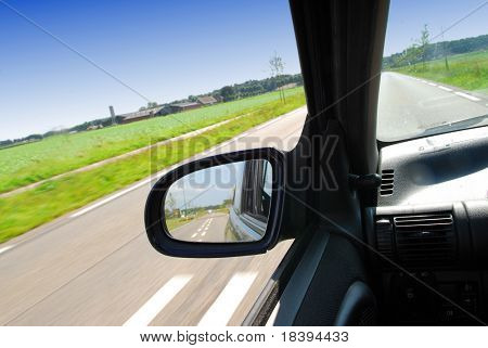 Rural landscape in the side-view mirror of a speeding car