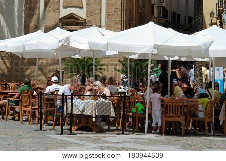 CADIZ, SPAIN - SEPTEMBER 8, 2008 - Tourists relaxing at pavement cafes in Cathedral Square Cadiz Cadiz Province Andalusia Spain Western Europe, September 8, 2008.