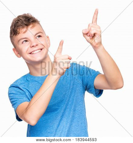 Half-length emotional portrait of caucasian teen boy. Funny teenager pointing and looking upwards while smiling, isolated on white background. Handsome happy child pointing at copy space.
