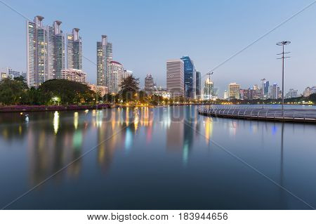 City office building view with refleciton over public park lake cityscape background