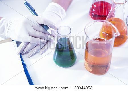Closeup of hands of Female Laboratory Worker Dealing With Flasks Containing Liquid Chemicals. Horizontal Composition