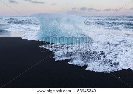 Ice cube breaking on black sand beach Iceland winter season lanscape background