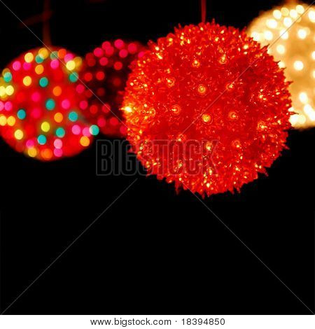 Colorful lights on christmas balls on black square background