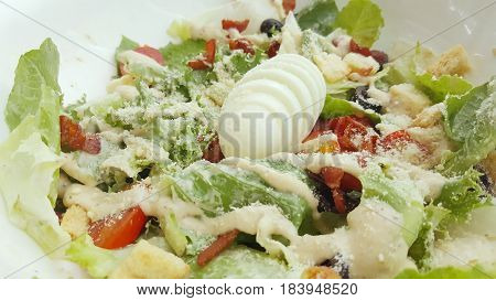 The salad consists of lettuce tomatoes biscuits cheese and many salads. Topped with dressing Look delicious