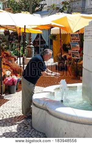 CADIZ, SPAIN - SPETMEBER 8, 2008 - Local man washing his hands in the marble fountain in the Plaza de las Flores with flower stalls to the rear Cadiz Cadiz Province Andalusia Spain Western Europe, September 8, 2008.