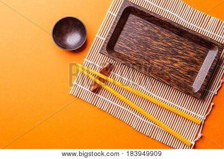 Image of set of dishes for sushi on orange background