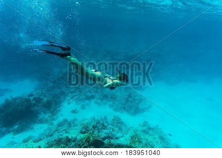 Underwater Shot Of The Young Lady Gliding Over Vivid Coral Reef On A Breath Hold In Sea