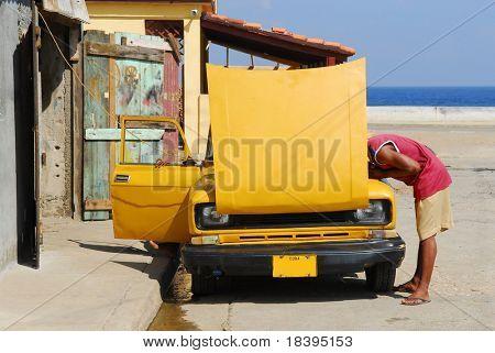 Cuban guy trying to fix his vintage american yellow car in Baracoa, Cuba