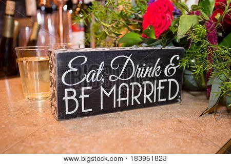 Sign at a wedding reception says eat drink and be married.