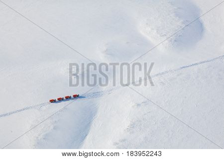 Trucks moving through out road in the snow covered tundra in vicinity of oil field, top view.