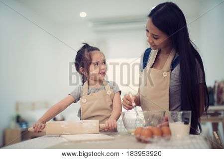 mother and daugthter cooking togather for make bread for dinner in kitchen room kid children