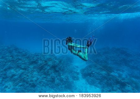 Underwater Image Of A Young Lady Snorkeling And Diving In A Tropical Sea With Hands On Legs.