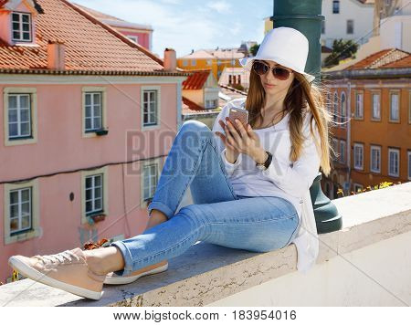 Young pretty girl in sunglasses texting on a cell phone in an urban environment on a sunny summer day