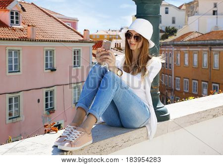 Young lovely woman in sunglasses texting on a cell phone in an urban environment on a sunny summer day