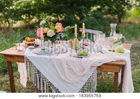 picnic, summer, holiday concept - beautiful decorated table at green lawn with trees, openwork white tablecloth, glassware, colorful bouquet of peony flowers and roses, fruits, candlesticks, lemonade