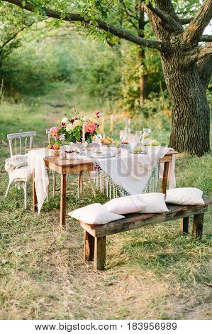 picnic, food, summer, holiday concept - festively decorated wooden picnic table among trees, bouquet, pitcher of lemonade, glasses, fruit plates, candlesticks, pillows and blanket on chairs and bench