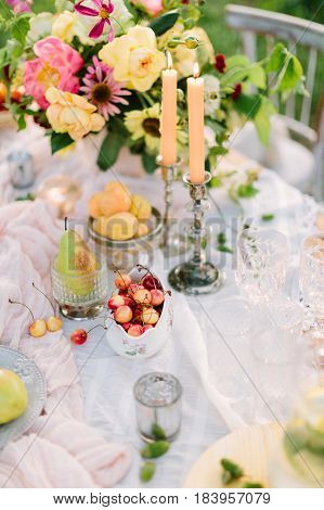 picnic, food, summer, holiday concept - close-up on part of decorated table with beautiful bouquet of roses and pink peonies, burning candles in candlesticks, fruits, glassware, decor of acorns