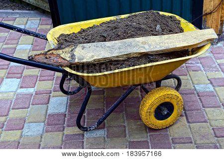 yellow garden wheelbarrow full of earth and debris
