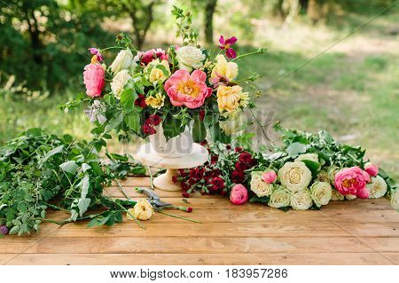 bouquet, holiday flower, gift and floral arrangement concept - composing a wonderful bouquet in white vase on wooden table in garden, cut flowers, white and yellow roses, pink peonies, red carnations