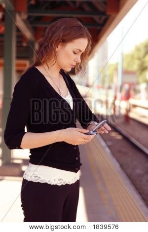 Young Woman Checks Watch While Holding Cell Phone