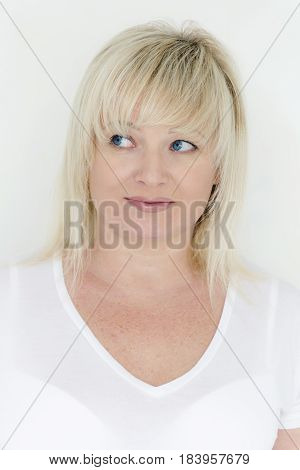 Vertical portrait of european blond woman with hair and blue eyes looking to left