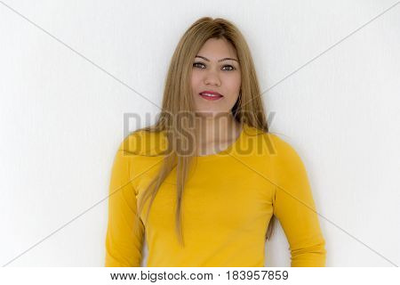 Young girl with long brown healthy straight hair in yellow