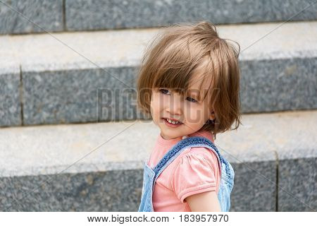 Portrait of baby girl on the stairs background