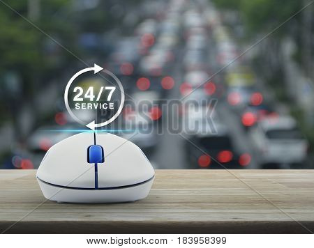 24 hours service icon with wireless computer mouse on wooden table over blur of rush hour with cars and road Full time service concept