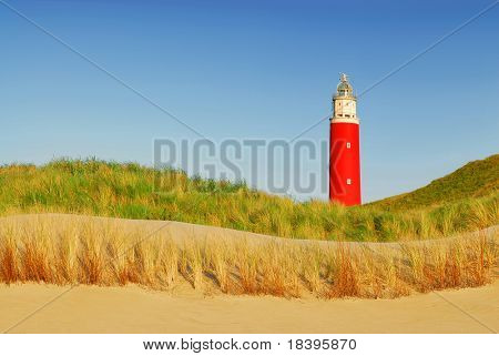 Lighthouse with dunes, beach and blue sky on dutch island Texel