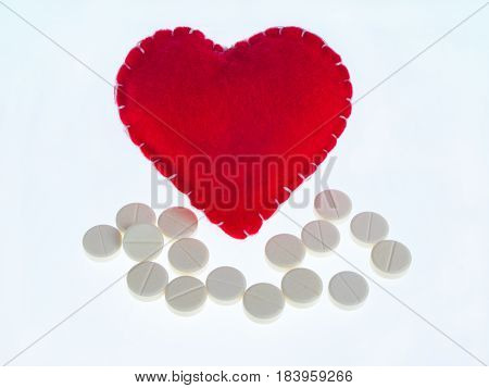 Red heart and white pills on white