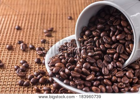 White cup full of coffee beans on the canvas