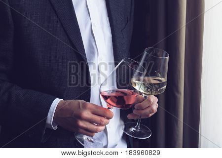 Horizontal close up of Caucasian man in black suit and white shirt holding two tall glasses with rose and white wine at an event by the window natural lighting