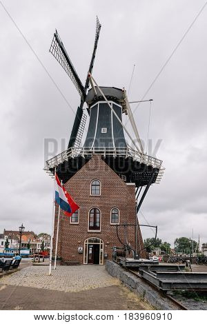 Haarlem, Netherlands - August 3, 2016: Picturesque cityscape with windmill in Haarlem