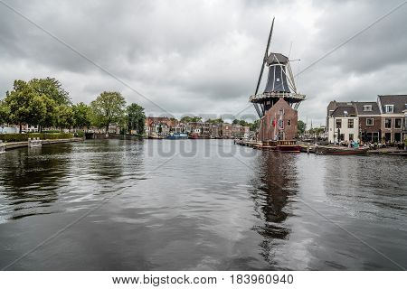 Haarlem Netherlands - August 3 2016: Picturesque cityscape with beautiful traditional house windmill and vessels in canal of Haarlem