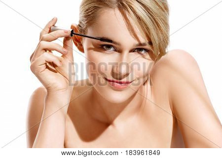 Charming smiling blonde applying mascara to her eyebrows. Photo of young woman finishing her makeup in the morning time. Beauty concept