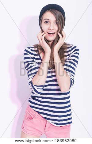 Youth LIfestyle Concepts. Portrait of Surprised Caucasian Brunette Girl in Hat and Striped Shirt. Posing Against White Background. Vertical Image Orientation
